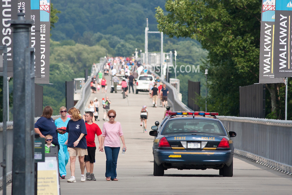 Highland, New York -  People walk past two New York State Police cars on the Walkway over the Hudson on the sunny summer afternoon of June 30, 2014. Walkway Over the Hudson State Historic Park is a linear walkway spanning the Hudson River. At 212 feet tall and 1.28 miles long, it is the longest, elevated pedestrian bridge in the world. The walkway was formerly an abandoned railroad bridge.