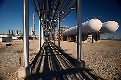 Stock photo of elevated pipes and storage tanks at a chemical plant