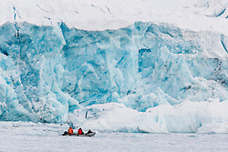 A zodiac with tourists in front of a glacier, Arctic Ocean, Svalbard, Norway