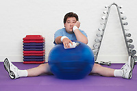Overweight Man sitting on floor with exercise ball in health club portrait