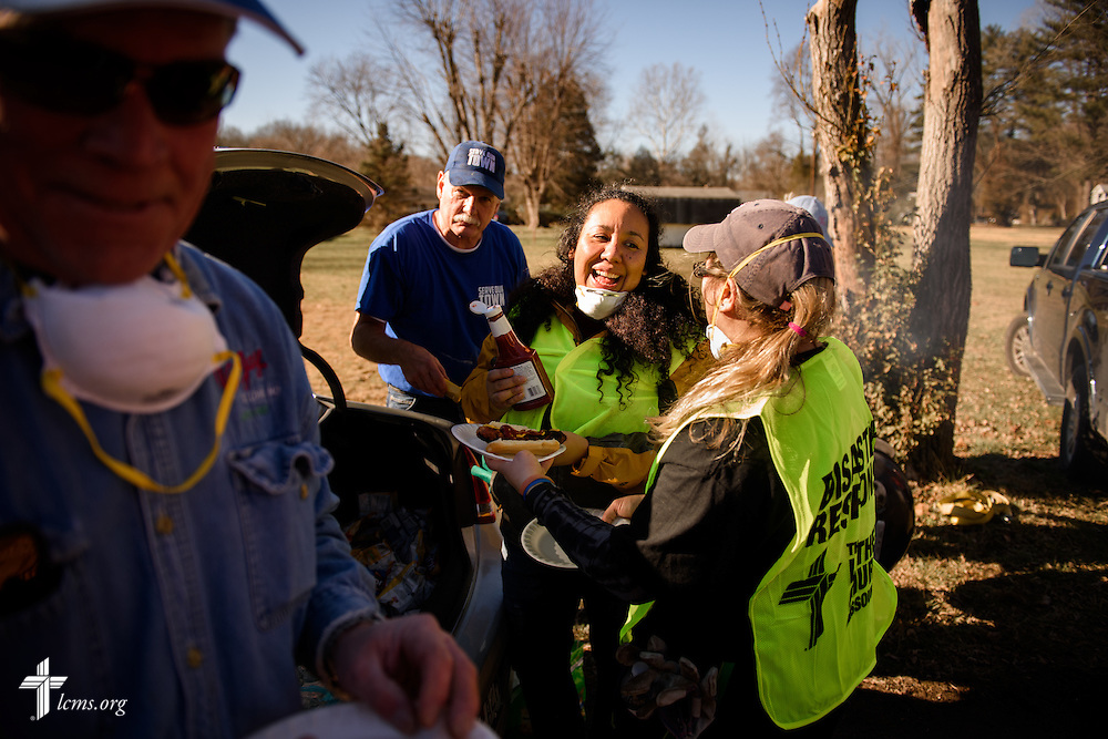 Mireya Johnson of LCMS Communications (center), joins other volunteers from the International Center of The Lutheran Church–Missouri Synod, New Beginnings Lutheran Church in Pacific, Mo., and Missouri representatives of the Southern Baptist Convention Disaster Relief, following a cleaning event at a flood-damaged home in Fenton on Thursday, Jan. 14, 2016. LCMS Communications/Erik M. Lunsford
