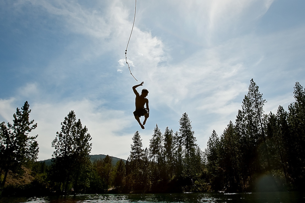 JEROME A. POLLOS/Press..Dustin Armstrong, 14, drops from the rope swing at Black Bay park into the cool water below Friday as temperatures hovered near the mid-90s.