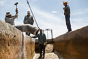 LA MESA, NM - APRIL 10, 2015:  A work crew chisels concrete to get a outlet to fit on a partially collapsed well on Phil Archer's, right, farm. Archer will have to replace the well soon, one of two on his farm. CREDIT: Max Whittaker for The New York Times