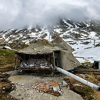 Remains of a camouflaged gun emplacement above a large bunker complex near the summit of the St. Gotthard Pass (2,106 m). The area belonged to the National Redoubt, the final Swiss line of defence in the high alps, and is checked with the remains of millitray installations, many of them underground, still camouflaged. The modern tunnels running far below are one of Europe's main transport routes, linking Italy to Northern Europe. The pass road is shut for months in winter due to heavy snow, only opening - mainly for tourism - in May.  The pass was one of the principal historic crossing points of the Alps, in use since the 13th century.
