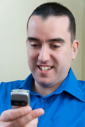 Man with a hearing impairment texting on his mobile phone,