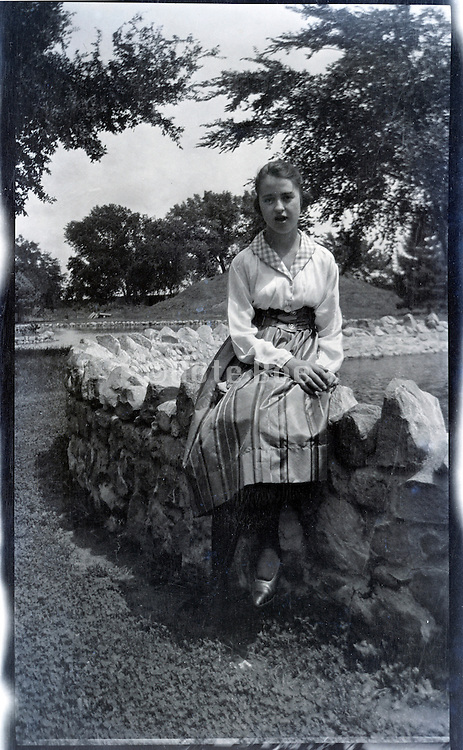 young adult girl sitting casually on a stone wall enclosure 1920s.