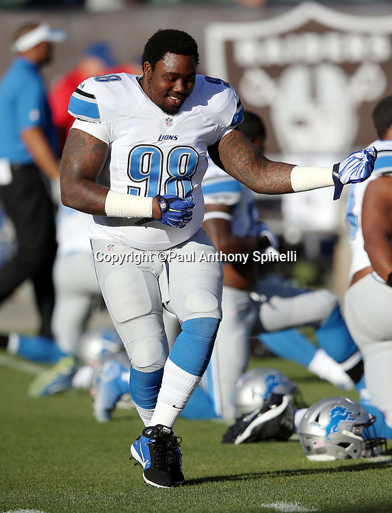 Detroit Lions defensive tackle Nick Fairley (98) plays air guitar while warming up before the 2014 NFL preseason football game against the Oakland Raiders on Friday, Aug. 15, 2014 in Oakland, Calif. The Raiders won the game 27-26. ©Paul Anthony Spinelli