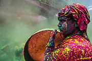 Drummer drenched in colors performing the ritual of Samaaj in Barsana during the festival of holi
