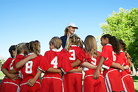 Group of children soccer players embracing standing in front of coach, back view