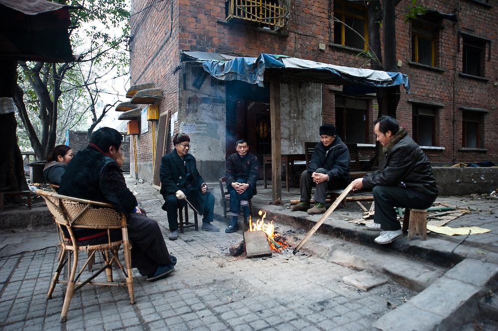 CHONGQING - JAN 18 2011: neighbours sit by the fire in a cold afternoon in the Jiulongpo district. They are the last remained living in the building  behind them that will be soon razed down to rise new buildings. Chongqing, China - The most populous city in the world