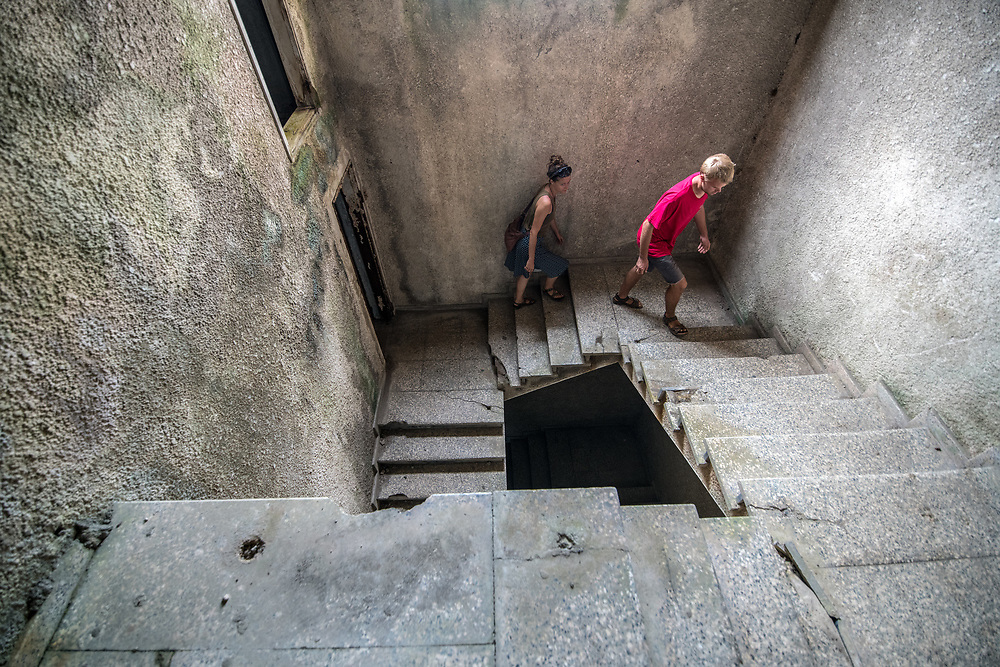 People walk up the stairs of the abandoned Ducor Hotel, once the most prominent hotels in Monrovia, Liberia