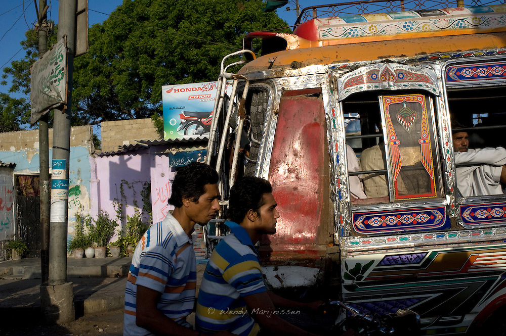 Two men on a motorcycle ride past a bus. Most buses and trucks in Pakistan are painted in the most lavish designs and colors, called truck art. Karachi, Pakistan, 2011