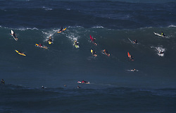 December 13, 2017 - Waimea Bay, Hawaii - Professional surfer John John Florence of Hawaii, center (green board) paddles into a large wave at Waimea Bay. The big wave surfing spot only breaks in the winter when storms send large north swells toward the North Shore of Oahu. (Credit Image: © Erich Schlegel via ZUMA Wire)