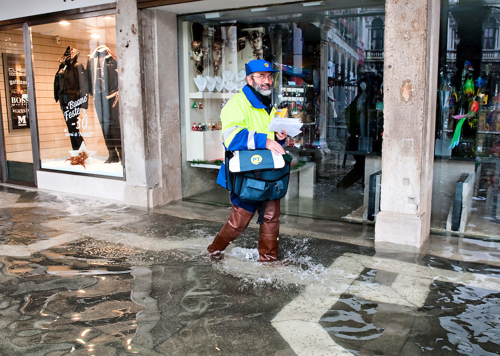 A postman on a delivery tour on a day of exceptional High Tide in Venice with water above 140cm covering more than 50% ot town Marco Secchi /xianpix<br /> msecchi@gmail.com