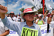 10 SEPTEMBER 2003 - CANCUN, QUINTANA ROO, MEXICO: Korean anti-globalization protestors march along the barricade separating the downtown area from the hotel zone in Cancun, Quintana Roo, Mexico during a protest against the WTO Wednesday. Lee Kyug-hae, one of the Korean protestors killed himself during the protest when he stabbed himself in the chest and then fell or jumped from a nearby rooftop. Tens of thousands of people opposed to the WTO have come to this Mexican resort city to protest the 5th Ministerial meeting of the World Trade Organization. The WTO meetings are taking place in the hotel zone of Cancun, about 10 miles from the protestors.  PHOTO BY JACK KURTZ
