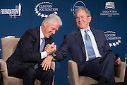 Former Presidents Bill Clinton (L) and George W. Bush shank hands after Bush gave Clinton advise on becoming a grandfather, during an event in Washington, D.C.