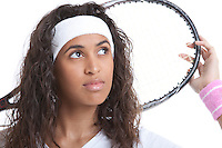 Sporty young woman with tennis racket looking away against white background