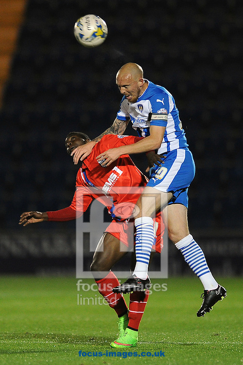 Sean Clohessy of Colchester United looks to win a header in the air against Jermaine McGlashan of Gillingham during the Johnstone's Paint Trophy match between Colchester United and Gillingham at the Weston Homes Community Stadium, Colchester<br /> Picture by Richard Blaxall/Focus Images Ltd +44 7853 364624<br /> 07/10/2014