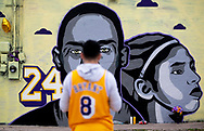Omar Garcia, wearing Kobe Bryant's jersey, takes in a new tribute mural honoring Kobe Bryant and his daughter, Gianna, on Thursday, Jan. 30, 2020, in Austin, Texas. The mural, located behind the Sushi Hi restaurant along Guadalupe Street, was created by Texas-based artist Laced and Found with help from Snuk One and Riki Loring. [NICK WAGNER/AMERICAN-STATESMAN]