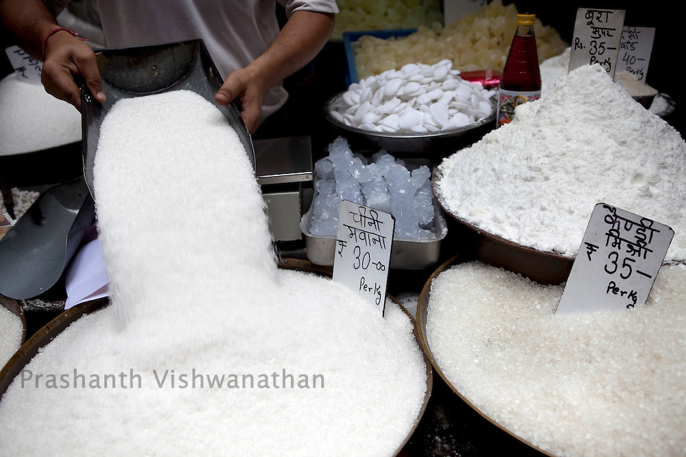 A shopkeeper refills stock, as he sells different varities of sugar at the busy wholesale market of Old Delhi, in New Delhi, India, on Wednesday September 2, 2010. Photographer: Prashanth Vishwanathan/Bloomberg News