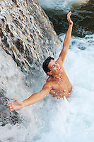 Young man standing under waterfall with arms outstretched high angle view