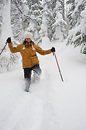 Low angle view of a mid adult woman in snowshoes with ski poles hiking down a snowshoe trail in deep powder in Bend, Oregon. (releasecode: jk_mr1034) (Model Released)