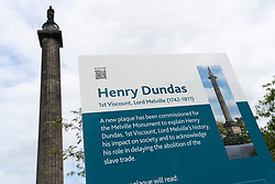 Edinburgh, Scotland, UK. 24 July, 2020. New sign beside monument to Henry Dundas in St Andrew Square. A new plaque is being installed to explain the controversial history of Henry Dundas and in particular his connection to the African slave trade.  Iain Masterton/Alamy Live News