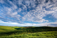 Beautiful puffy clouds in the sky above the rolling hills of the Orcia Valley, Tuscany. Taken on a sunny morning at the end of april