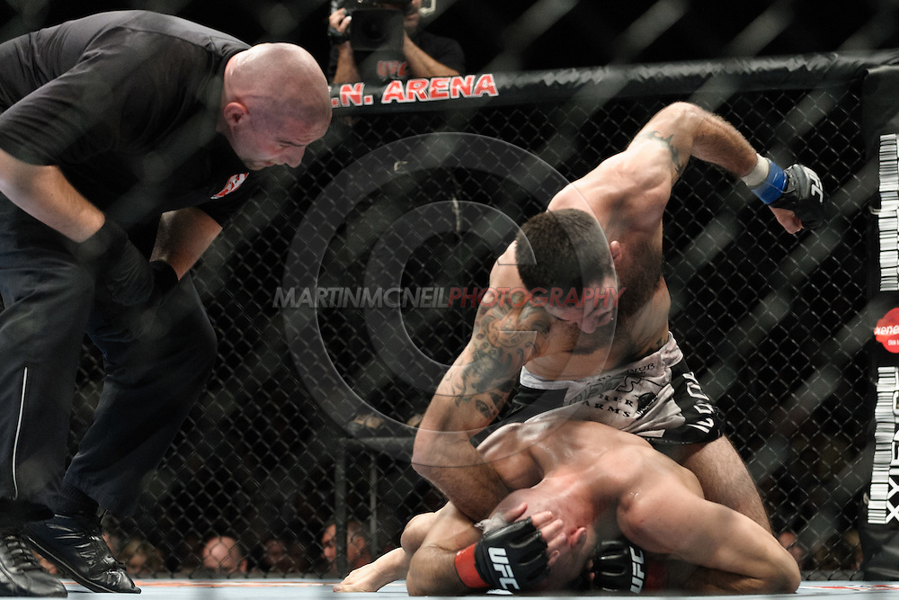 """MANCHESTER, ENGLAND, NOVEMBER 14, 2009: Referee Leon Roberts (left) prepares to intervene as Matt Brown (top) rains down blows on James Wilks during """"UFC 105: Couture vs. Vera"""" inside the MEN Arena in Manchester, United Kingdom."""