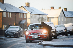 © Licensed to London News Pictures. 30/01/2019. High Wycombe, UK.  A woman scrapes snow and ice from her windscreen in High Wycombe, Buckinghamshire, as snow hits the south east of England. Photo credit: Ben Cawthra/LNP