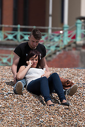 © Licensed to London News Pictures. 01/06/2014. Brighton, UK. A couple enjoy the sunshine on Brighton Beach. Despite a good start to the weekend on Saturday the weather has deterred some people from coming to the beach. Photo credit : Hugo Michiels/LNP