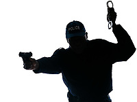 Silhouetted Afro American policeman aiming handgun while holding handcuffs isolated on white background
