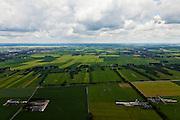 Nederland, Overijssel, Gemeente Twenterand, 30-06-2011; Landschap ten noorden Vriezenveen, links Vroomshoop, rechts esterhaar-Vriezeenveenswijk. Voorbeeld van vroege ruilverkaveling (jaren '50). De oorspronkelijk (zeer) smalle en lange kavels, ontstaan door het ontginnen van veen, zijn samengevoegd tot grotere blokken en veelal is het kavelpatroon 90 graden gedraaid. De globale oorspronkelijke - onderliggende - structuur is deels nog herkenbaar..Kenmerkend zijn verder de 'boerderijstraten', linten van boerderijen omgeven door singels van bomen (in het midden)..Landscape north of Vriezenveen, an early example of land consolidation (50s)..The original (very) long and narrow lots, created by the extraction of peat, are merged into larger blocks and in most cases the plot pattern has been rotated 90 degrees  The original - underlying - structure is still partly visible..Further characteristic features are the 'farm roads' with farmhouses surrounded by belts of trees..luchtfoto (toeslag), aerial photo (additional fee required).copyright foto/photo Siebe Swart