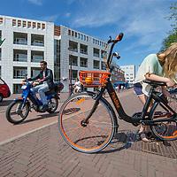 Nederland, Amsterdam, 9 juli 2017.<br /> De Amsterdamse start-up FlickBike test deze zomer een naar eigen zeggen &lsquo;vernieuwend deelfietsconcept&rsquo;. Het experiment omvat duizend fietsen, die realtime te vinden zijn via een gratis app. Gebruikers downloaden de app, zoeken een fiets in de buurt en openen het fietsslot met hun telefoon.<br /> <br /> Anders dan bij veel bestaande deelfietsconcepten, laten fietsers een FlickBike gewoon achter op hun bestemming. Teruggaan naar een huurstalling of fietsverhuurstation is niet meer nodig.<br /> Op de foto: Meisje verstelt haar zadel vd Flick bike<br /> <br /> <br /> Foto: Jean-Pierre Jans