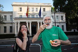 "© Licensed to London News Pictures . 18/07/2013 . London, UK. Spanish citizens living in London protest against Federico Trillo-Figueroa, the Spanish ambassador to Britain, outside the Spanish Embassy in Belgrave Square, London. They eat chorizos - spicy sausages- which mean ""thieves"" in Spanish slang as a symbol of the Government's corruption. Mr Trillo-Figueroa has been accused of receiving €128,000 from a secret slush fund while serving as Defence Minister for the centre-right Popular Party (PP) Government of José Maria Aznar, former Prime Minister. The accusations were made by former treasurer of the Popular Party Luis Bárcenas, who is currently awaiting a trial on fraud charges.Photo credit : /LNP"