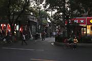 """Soirée du 11 septembre 2011, au croisement de  Dongsi beidajie et Xiang'er hutong. A gauche le salon d'un coiffeur aux allures modernes avec des plafonniers en ampoules géantes qui ont peut-être été achetées au quincailler d'à côté qui propose aussi  tubes pour canalisations en pvc et prises électriques. Dans la ruelle un restaurant ouighour intitulé """"Le gôut du Xinjiang"""" et son barbecue extérieur désormais doté d'une hotte aspirante , suivi de toilettes publiques et plus loin d'une autre enseigne lumineuse indiquant aussi la vente de brochettes. Sur la droite, dans l'ombre des platanes, un kiosque à journaux avec une publicité pour la version chinoise de Vogue devant la boutique d'une chaîne de douceurs et pâtisseries  nommée """"Hao Lilai""""."""