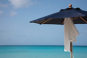 Anguilla, British West Indies, Caribbean - White beach towel swings in the breeze from a Navy blue resort umbrella in front of the Turquoise water of Rendezvous bay.