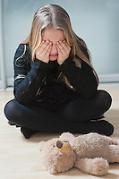 Young girl sitting on floor with hands on eyes