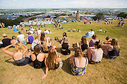 The sun continues to shine on the second day of Glastonbury Festival after it opened it's gates yesterday for the early arrivals. Approximately 170,000 revellers are set to turn up to the festival which is hosting a number of headliners including Kanye West and Alt J. <br /> Pictured: Festival goers enjoy the sunshine overlooking Glastonbury Festival on day two.