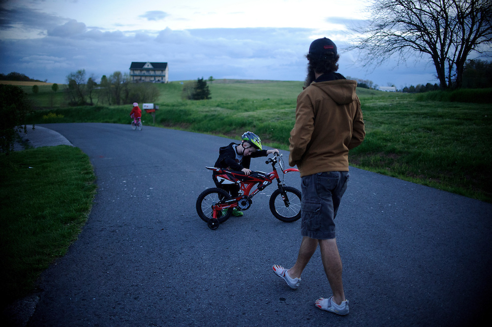 photo by Matt Roth.Wednesday, April 11, 2012..Ron Shriver watches over his children Miles and Rory while they ride bikes at dusk Wednesday, April 11, 2012. Ron Shriver likes his children to play before bed so they're more likely to go to sleep. ..Ron Shriver grew up on a large farm house in Pleasant Valley, Maryland, a small township outside Westminster. After his lease was up, he moved back to his parent's home with his two children Rory and Miles, living temporarily in their basement before graduating from McDaniel College in May. After tossing his graduation cap, he and his children will drive cross country to meet up with his wife who has been working on her graduate degree in Alaska. ..Ron Shriver is a retired marine staff sergeant. He is also the first in his family to attend college, thanks to the New G.I. Bill. His wife, a fellow retired Marine, is finishing up graduate school in Alaska. After Ron gets his undergraduate degree from McDaniel College in May, he plans to drive to Alaska with is two children Rory, 6, and Miles, 5. For the move Ron got rid of most of his family's belongings, and after his lease was up, he and his children moved back into his parent's farmhouse.