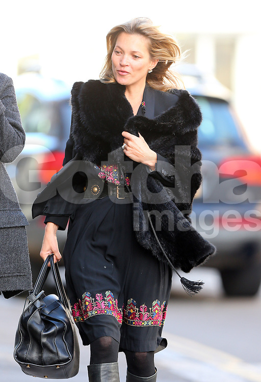 Kate Moss out on a windy day in North London. The supermodel wearing a black fur coat, black dress a knee high boots enjoyed a Japanese lunch with a friend. UK. 30/10/2013<br />