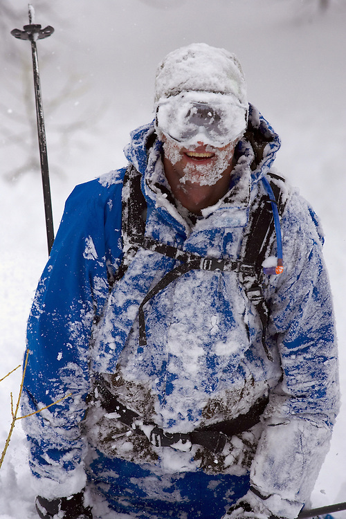 A Skier laughs after crashing in the powder and being covered in snow