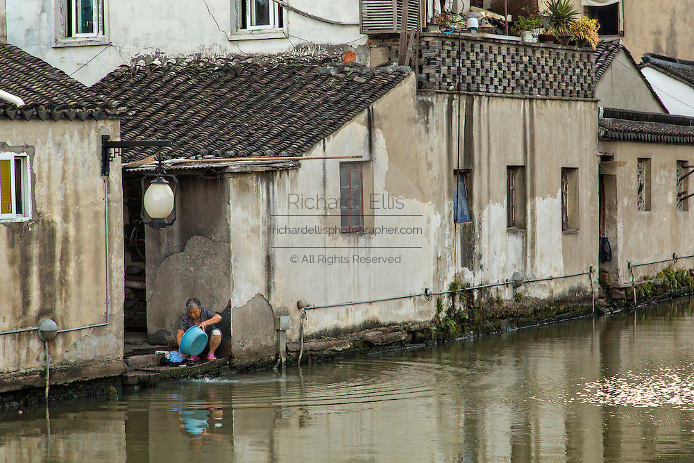 Elderly woman washes clothes along Shantang canal in Suzhou, China.
