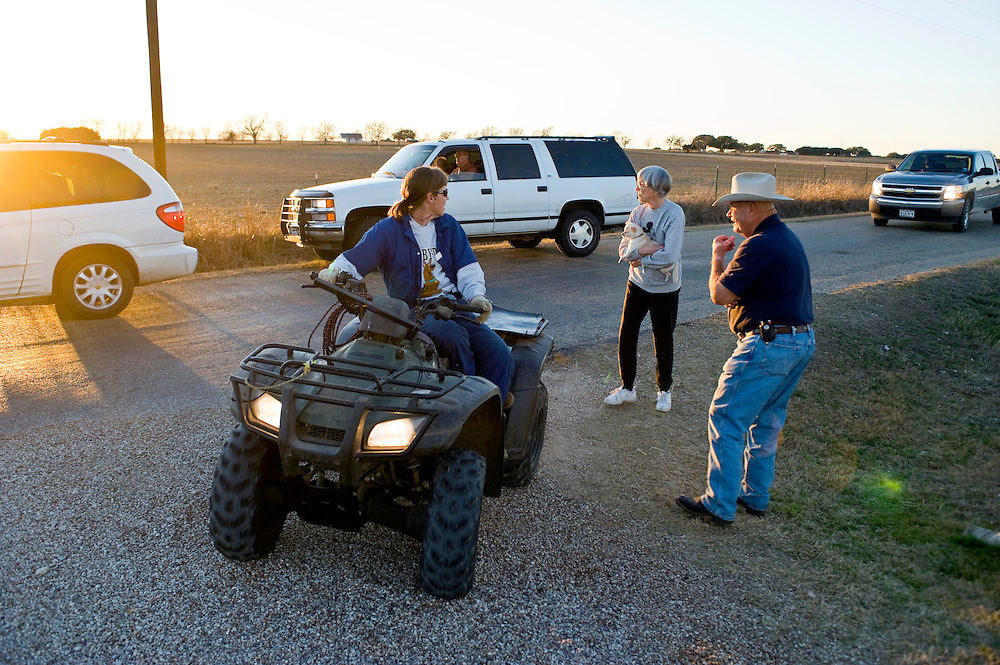 Crawford, Texas, USA.vlnr: Die Farmer und Nachbarn der Bush Ranch, Jerry Lynch, Billy Lynch (71) und Keith Lynch (71), mit Touristen Autos auf der Strasse vor ihrer Farm. Viele fragen nach dem Weg zur Ranch von Bush..left to right:.Farmers and neighbors of Bush, Jerry Lynch, Billy Lynch (71) and Keith Lynch (71) at their farm, with tourists driving by. Many stop and ask for the way to the Prairie Chapel Ranch..Crawford, Texas, is the hometown of outgoing President George W. Bush, who bought the Prairie Chapel Ranch, located seven miles (10 km) northwest of town, in 1999. The farm was considered the Western White House of the President, who is leaving soon for a new home in  Dallas. His departure will bring major changes to this small town (population: 705), which had in part made a living by catering to the tourist, press and protesting crowds that came to visit. At the same time they are very tired of it all and seem to be glad that life can finally get back to normal now...©Stefan Falke