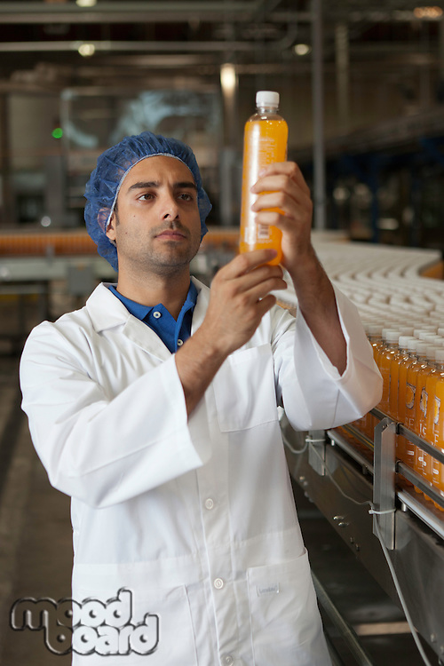 Factory worker examining orange juice bottle