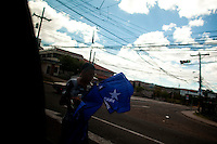 A young boy peddles political flags for the National Party Sunday, Nov. 29, 2009 in Tegucigalpa in Honduras. After months of turmoil following the Coup of former President Manuel Zelaya Honduras finally gets its chance to vote for the general elections that many hope will put the previous months behind them and return to normal.   Darren Hauck For The New York Times
