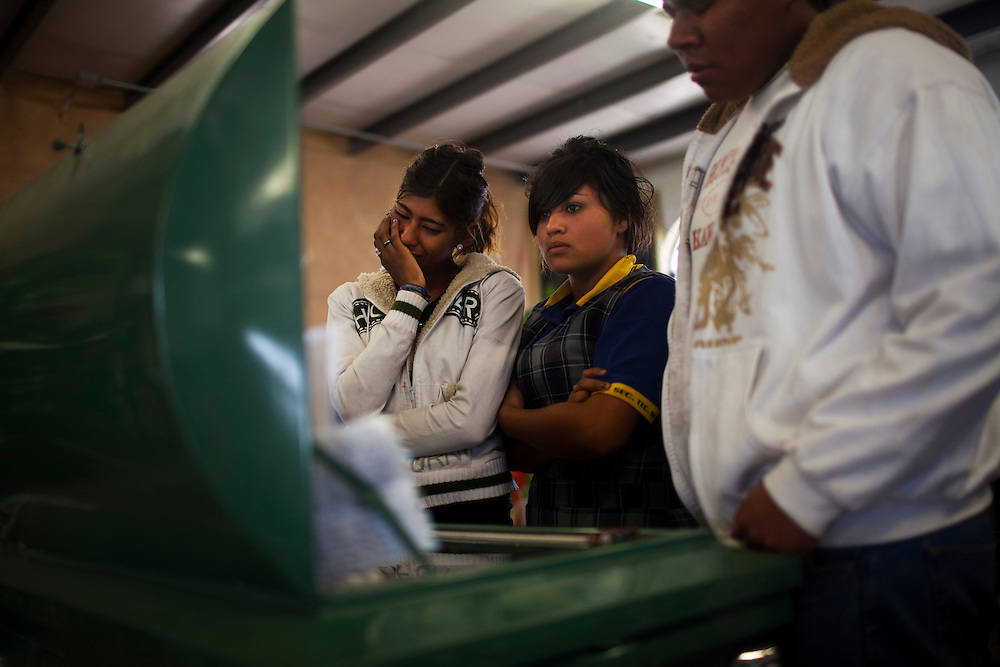 Friends of a teenager who was shot and killed at a birthday party mourn during a funeral.  15 kids total were killed during the massacre in Ciudad Juarez.