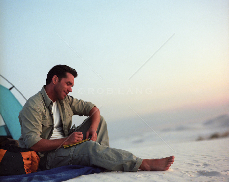 man writing in a journal while camping in White Sands National Park in New Mexico
