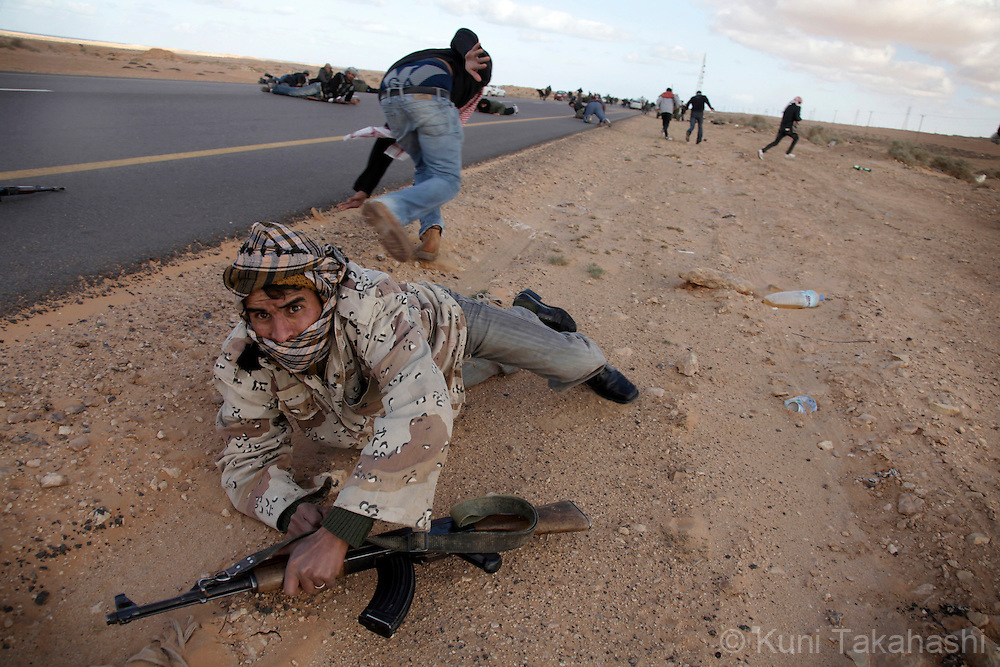 Rebel militia agasint Col. Muammar Gaddafi lay flat on the ground trying to take cover from bullets during the fight against Gaddafi's army in Ben Jawat on March 6, 2011. The government troop re-took the town Sunday. .Photo by Kuni Takahashi
