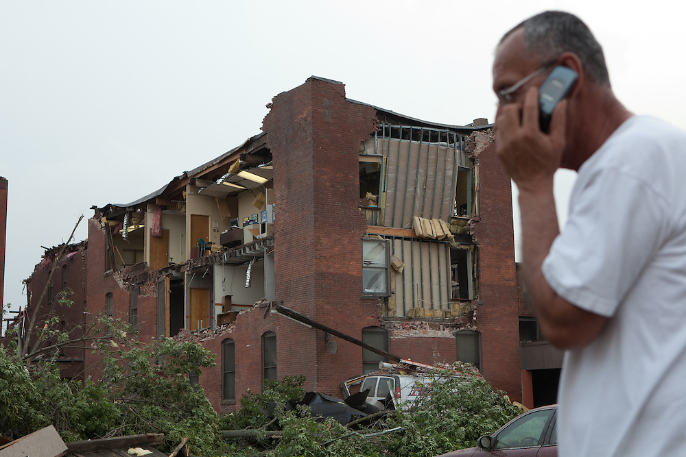 A man talks on his mobile phone near a storm damaged building on Hubbard Ave in downtown Springfield, MA where a tornado struck on Wednesday afternoon June 1, 2011.  (Matthew Cavanaugh for The Boston Globe)